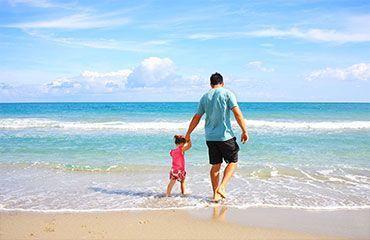 Padre niña orilla mar playa