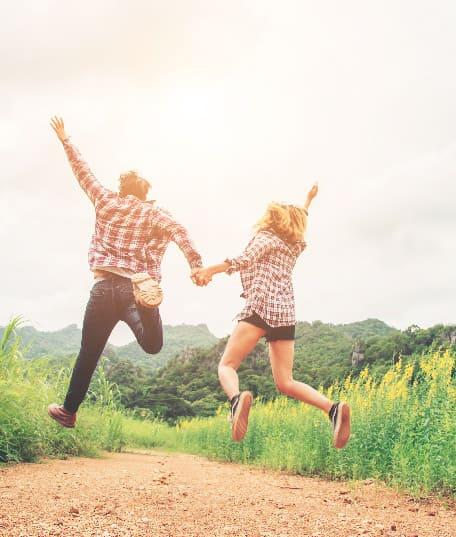 pareja saltando felices en el campo
